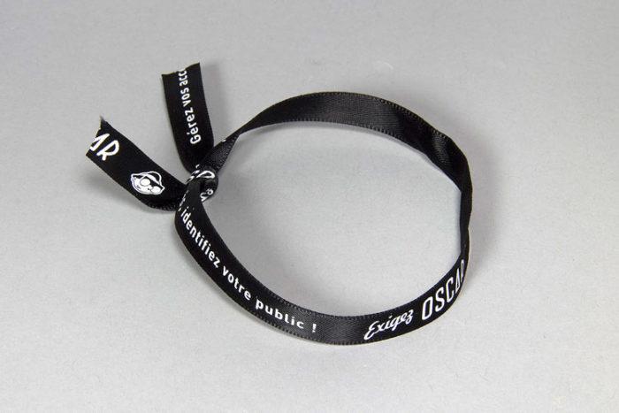 Bracelet en satin noir imprimé en blanc - Oscar Productions Nantes billetterie et gestion d'accès sécurisée